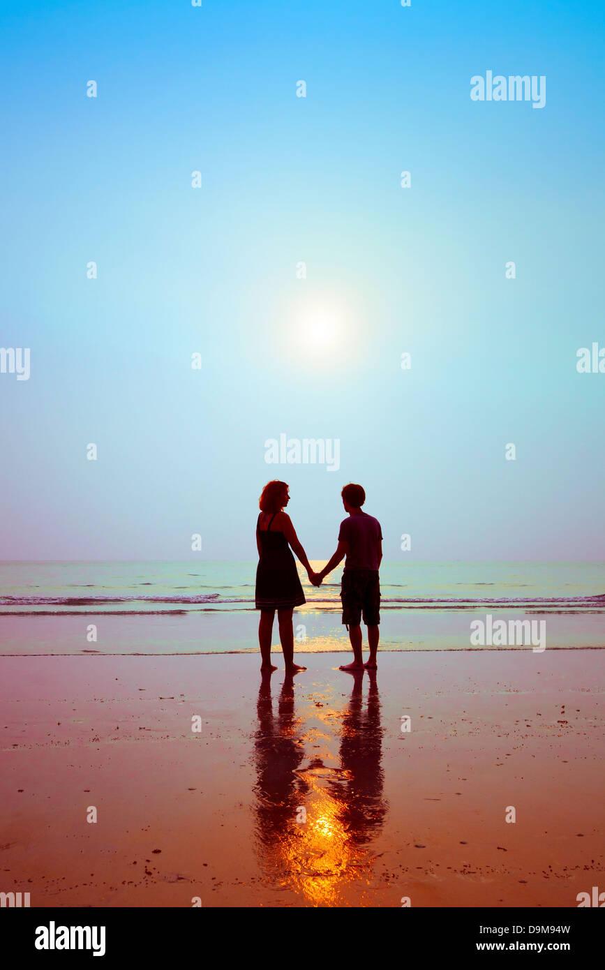 Flitterwochen, Silhouetten von Liebespaar am Strand Stockbild