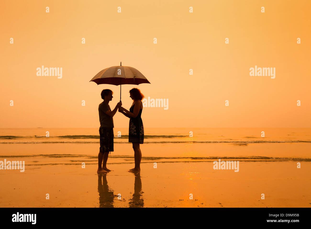 Familie am Strand, Silhouetten des Paares mit Regenschirm Stockbild