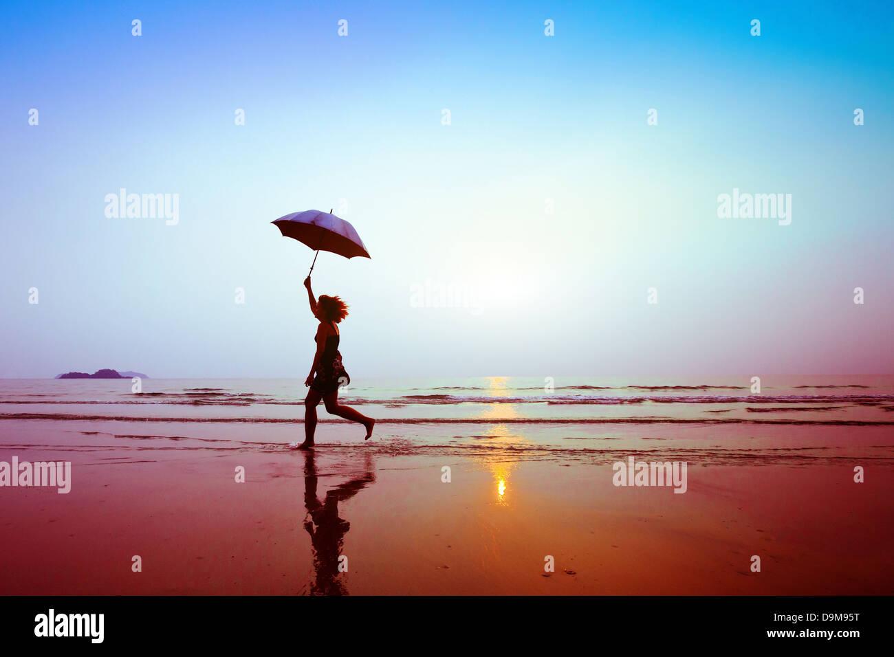 Silhouette der glücklich läuft Frau mit Regenschirm Stockbild