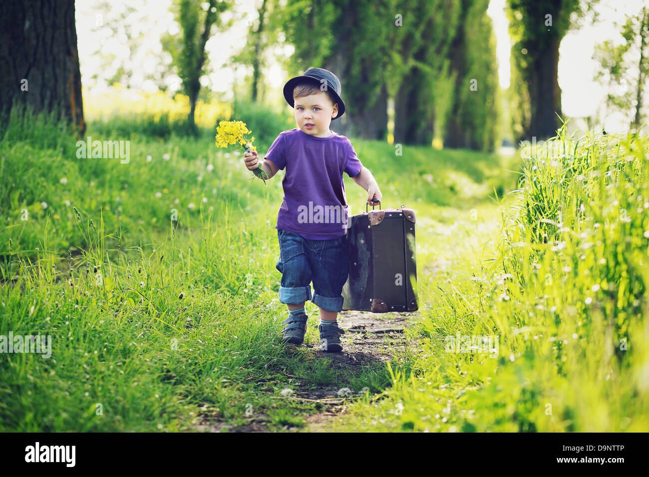 Kleiner Gentleman mit großen Koffer Stockbild