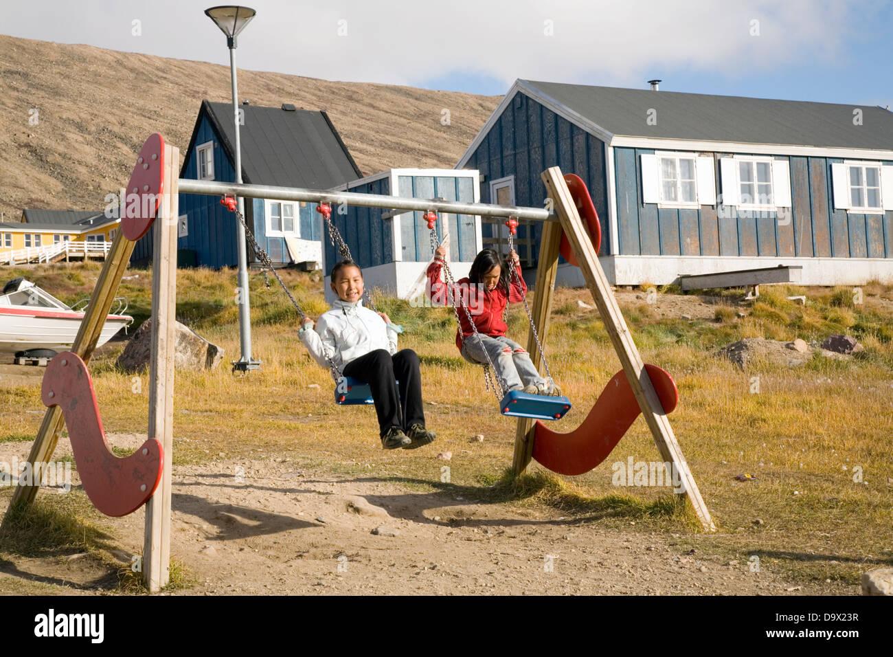 Kinder spielen auf einer Schaukel in Qaanaaq, Grönland Stockbild