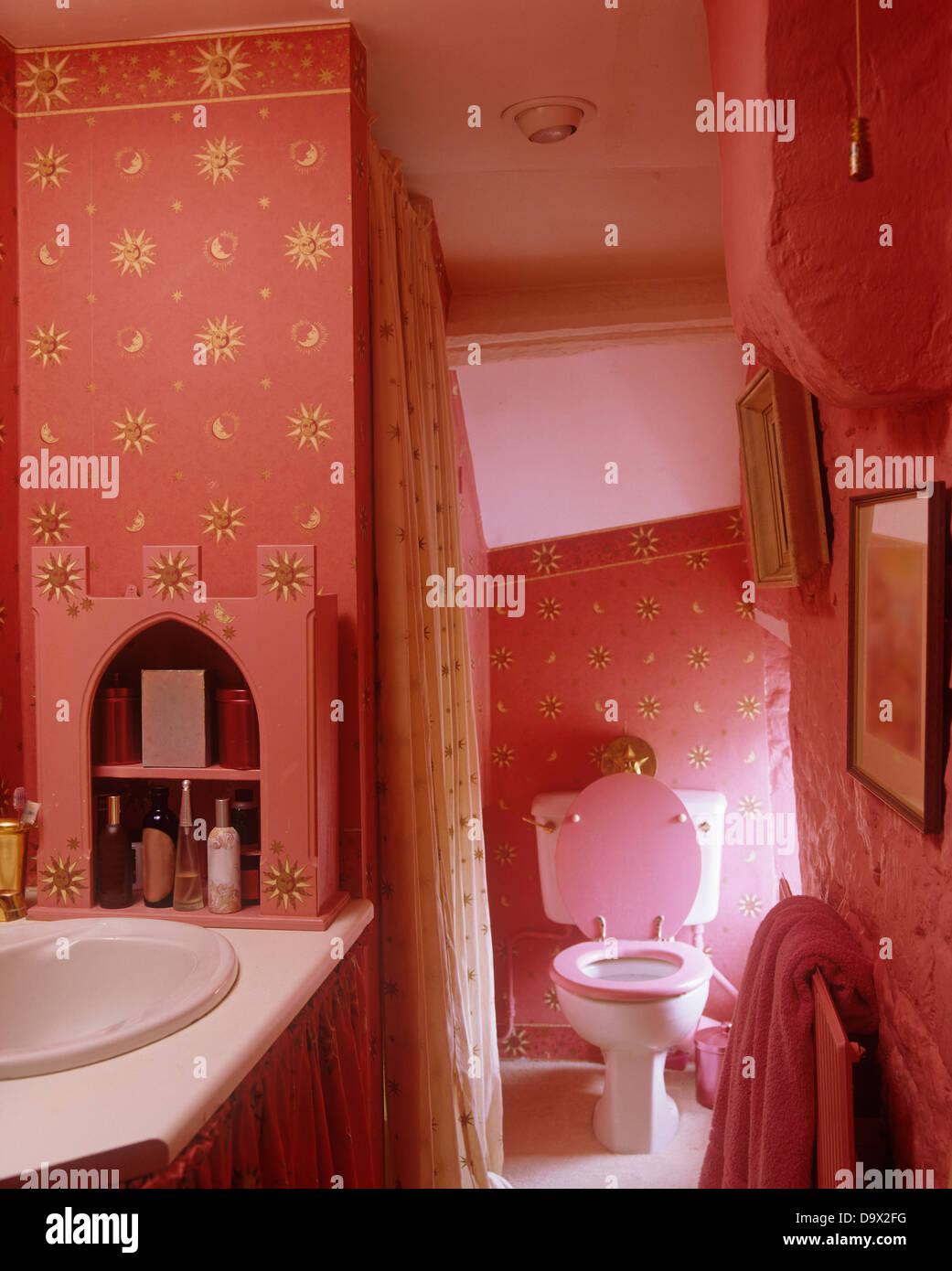 Waschbecken im Badezimmer mit tief rosa Tapete mit gold Stern