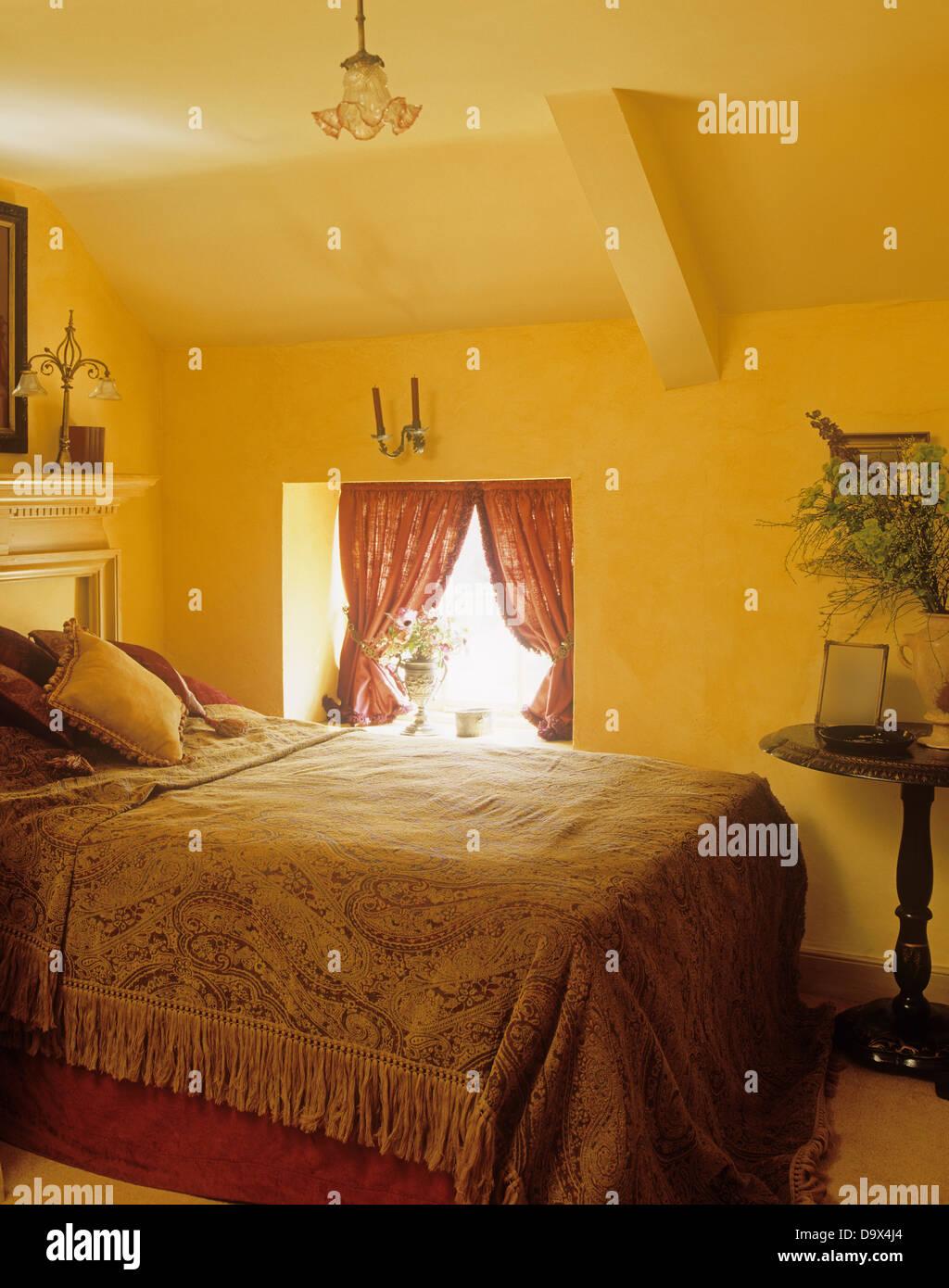 doppelbett mit fransen bettdecke in gelben land schlafzimmer mit schr gen decke stockfoto bild. Black Bedroom Furniture Sets. Home Design Ideas