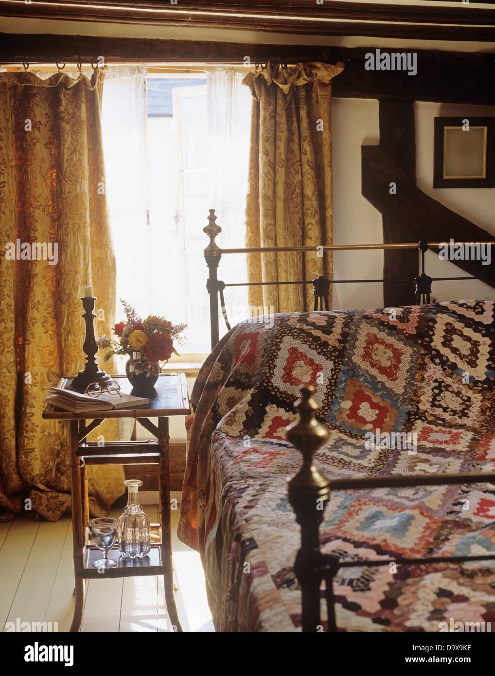 kleinen bambus tisch neben messingbett mit patchwork quilt im land schlafzimmer mit schweren. Black Bedroom Furniture Sets. Home Design Ideas
