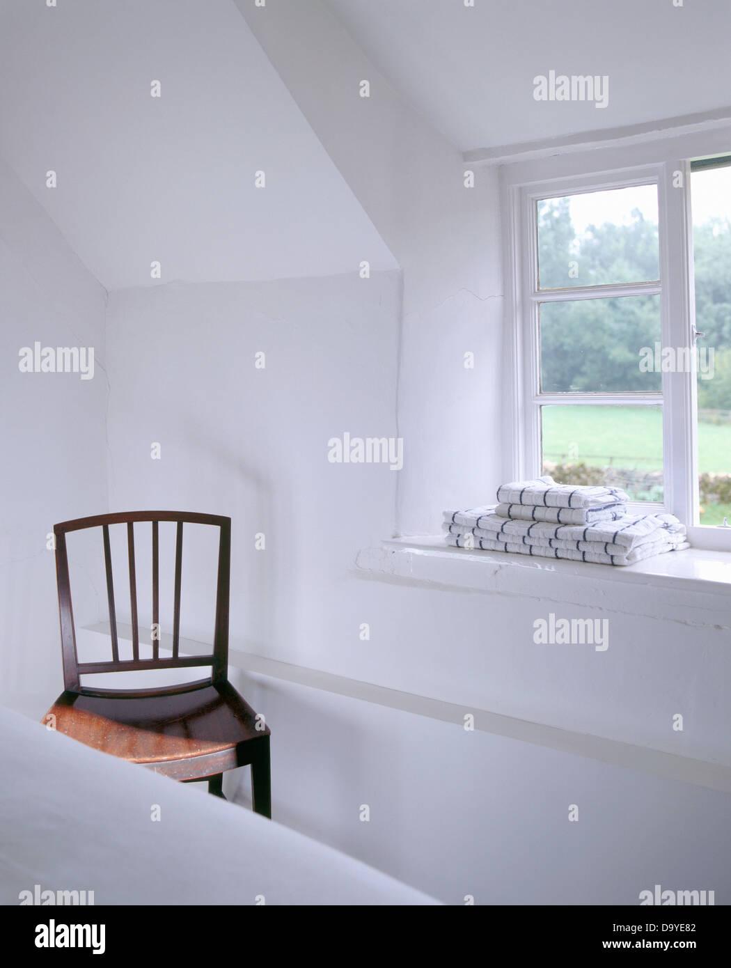 Holzstuhl Neben Offenen Fenster Mit Stapel Handtücher Auf Fensterbank In  Weißen Land Schlafzimmer Mit Schrägen Decke