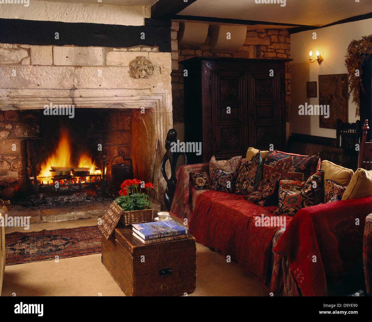 Roten Wurf auf Sofa mit Kissen neben Kamin mit offenem Kamin im ...