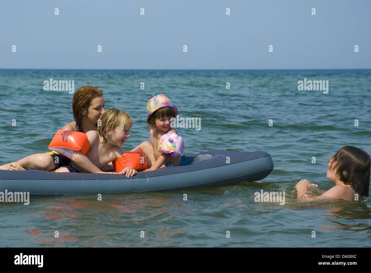 Fröhliche Kinder spielen auf einer Luftmatratze in der Ostsee Stockfoto