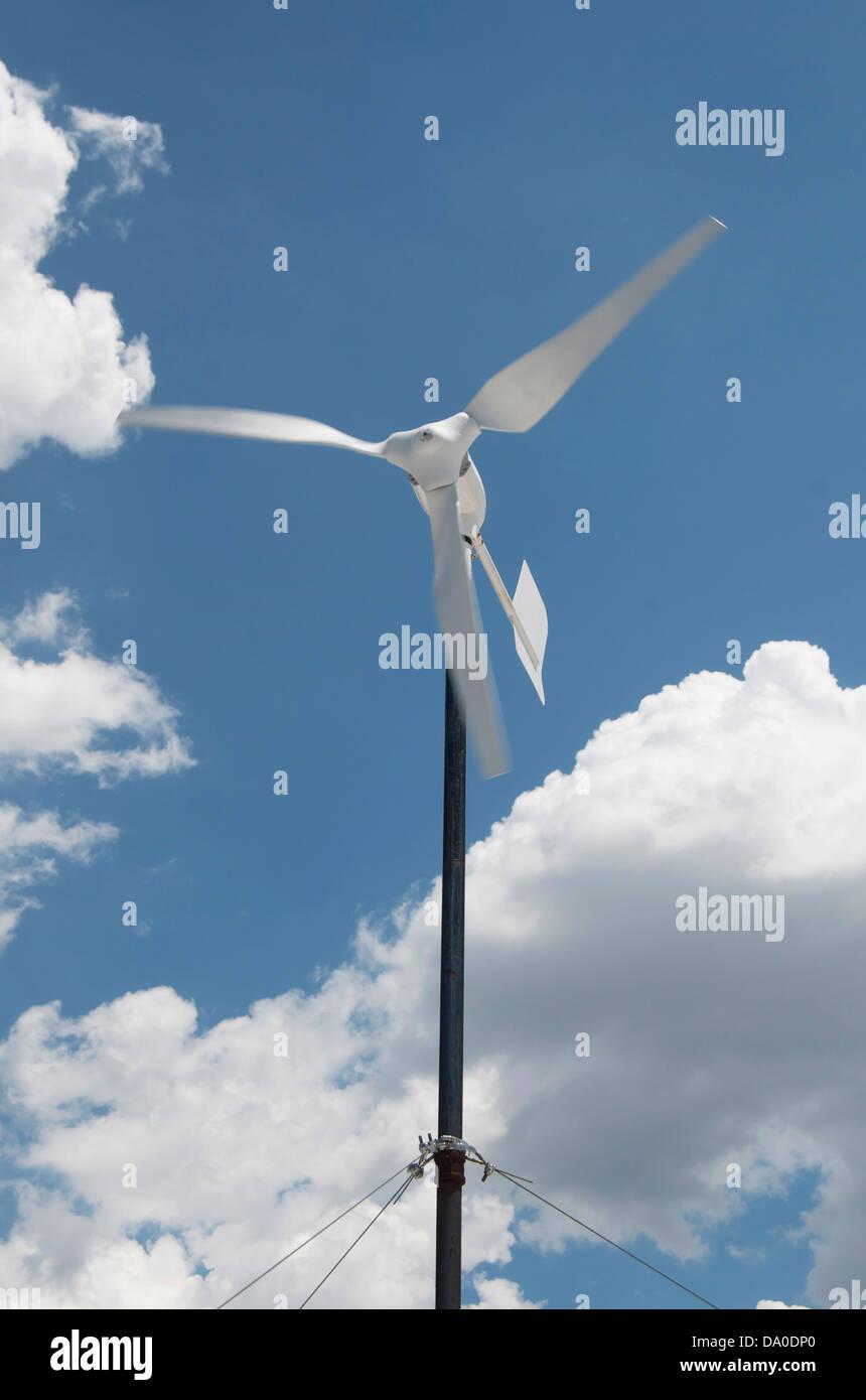 Energie erzeugenden weißer Windgenerator mit blauem Himmel und weißen Wolken an einem sonnigen Tag. Stockbild