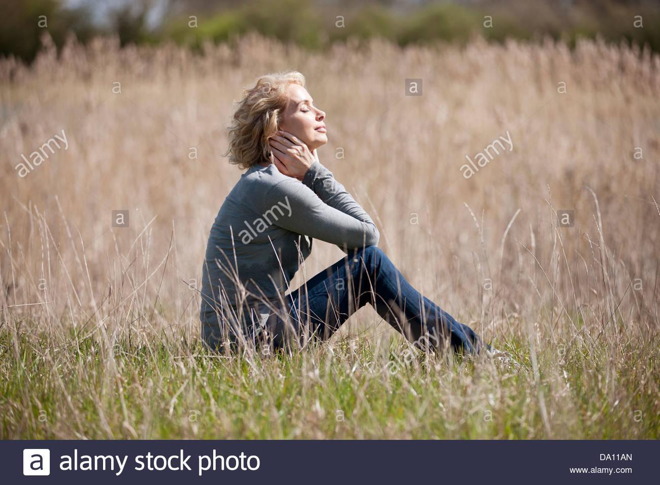Eine reife Frau sitzen auf dem Rasen, die Sonne zu genießen Stockbild