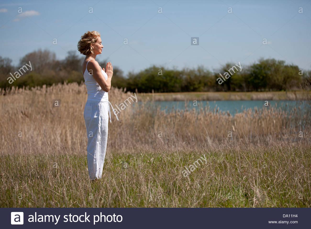 Eine Mitte Frau praktizieren Yoga auf dem Lande im Sommer Stockbild