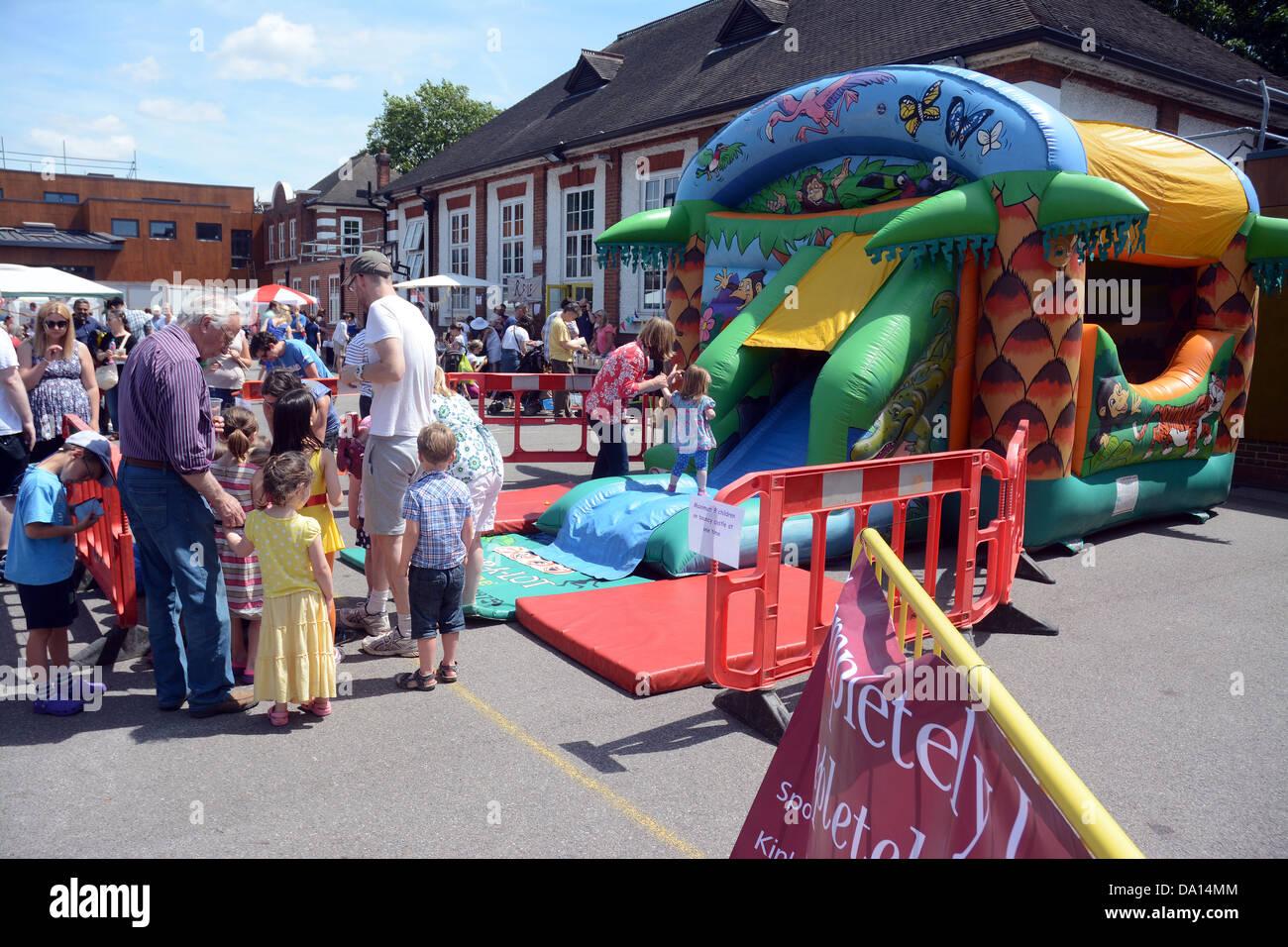 Eltern und Kinder warten auf eine Hüpfburg in einer Grundschule Sommer Messe gehen Stockbild
