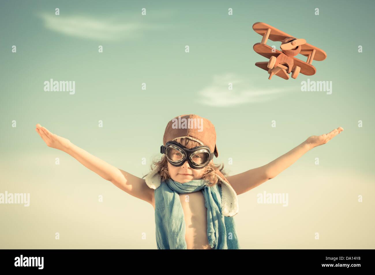 Glückliches Kind mit Spielzeugflugzeug gegen blauen Himmelshintergrund spielen. Vintage getönt Stockbild