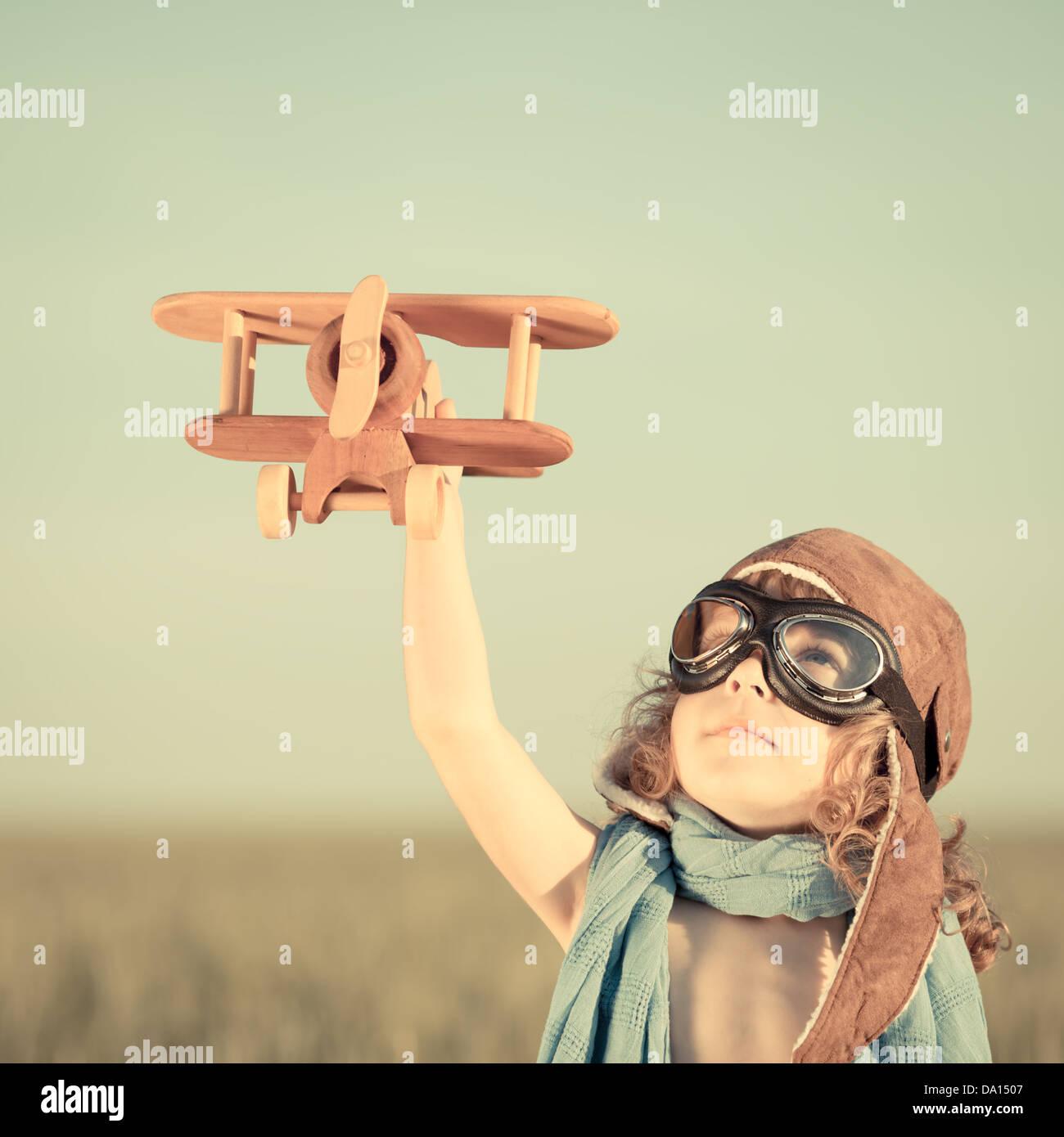 Glückliches Kind mit Spielzeugflugzeug gegen blauen Himmelshintergrund spielen. Stockbild