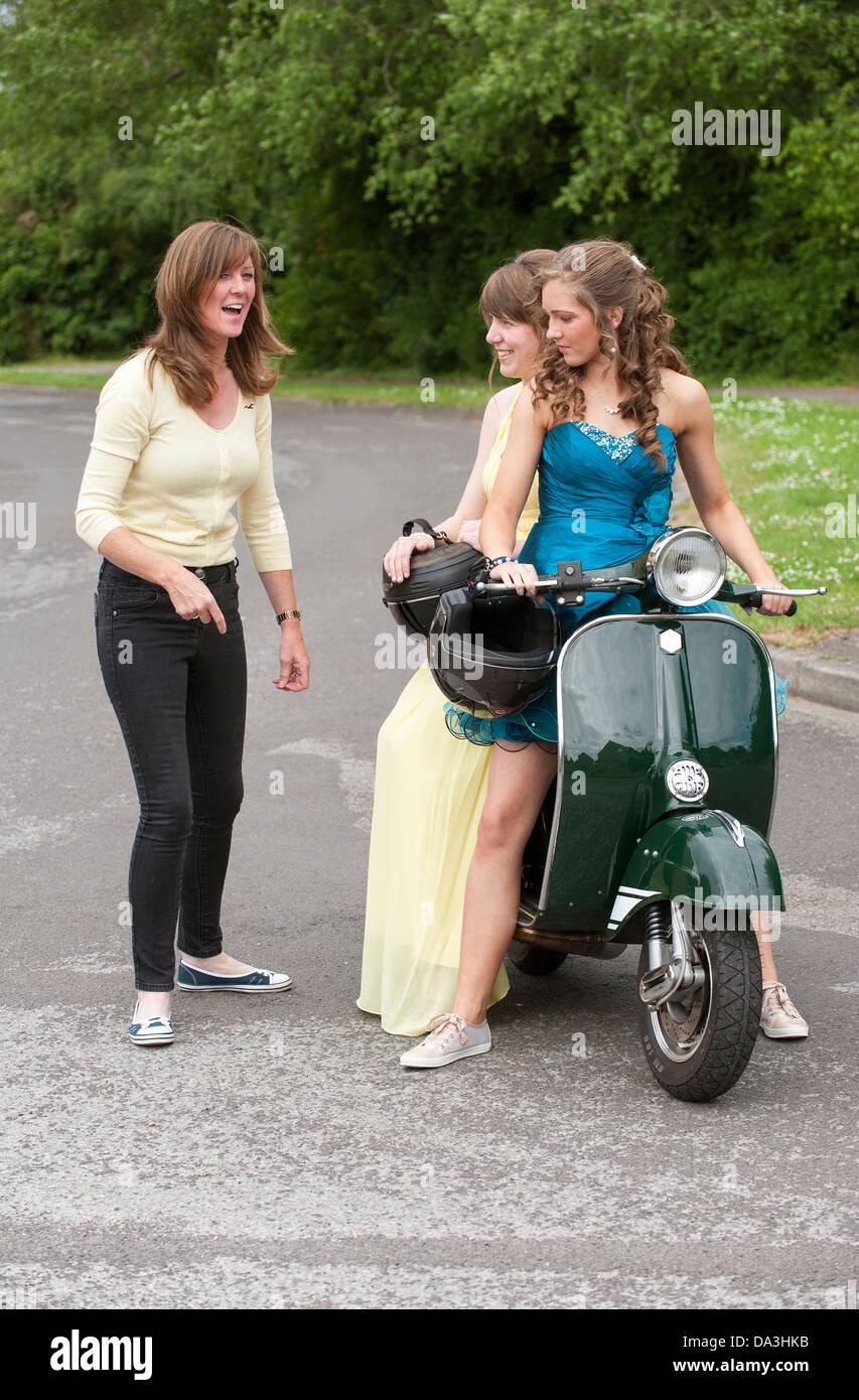 Zwei Junge Madchen Auf Motorroller Partykleider Tragen Nutzen Sie Last Minute Chat Von Mutter Stockfotografie Alamy
