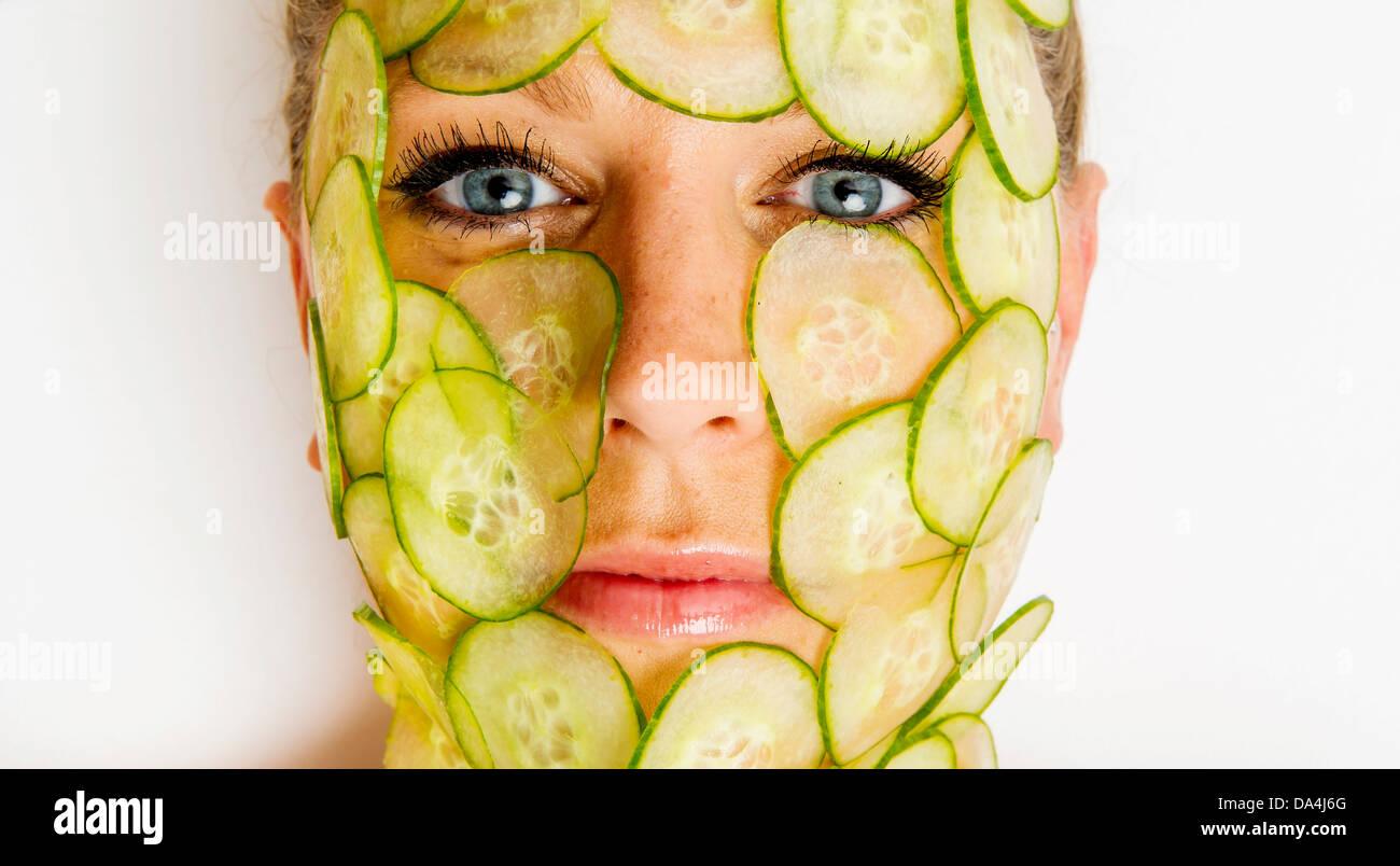 Frau mit Gurkenscheiben für ihr Gesicht Stockfoto