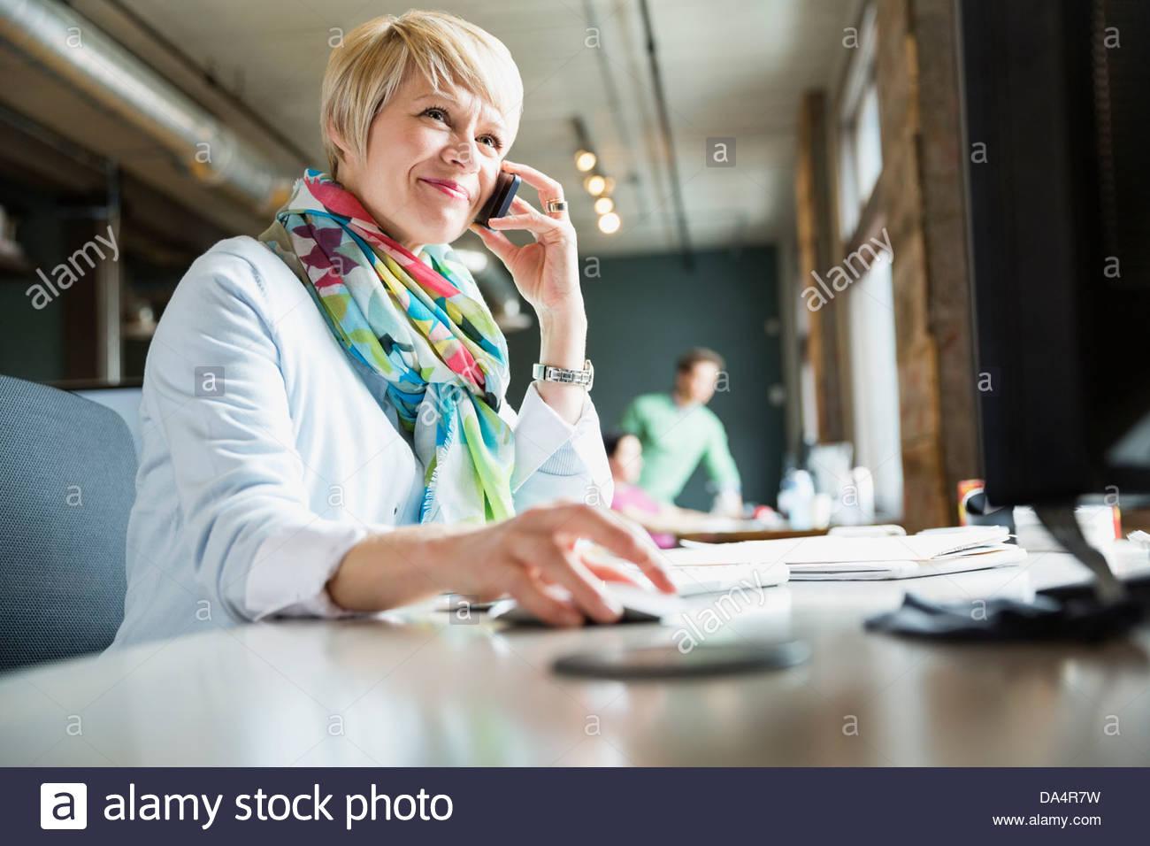 Unternehmerin mit Handy am Schreibtisch Stockbild