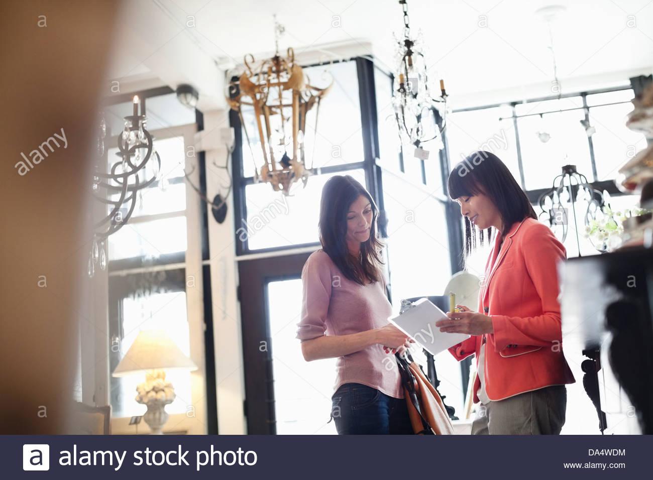 Weibliche Unternehmer helfen Kunden im Möbelhaus Stockbild