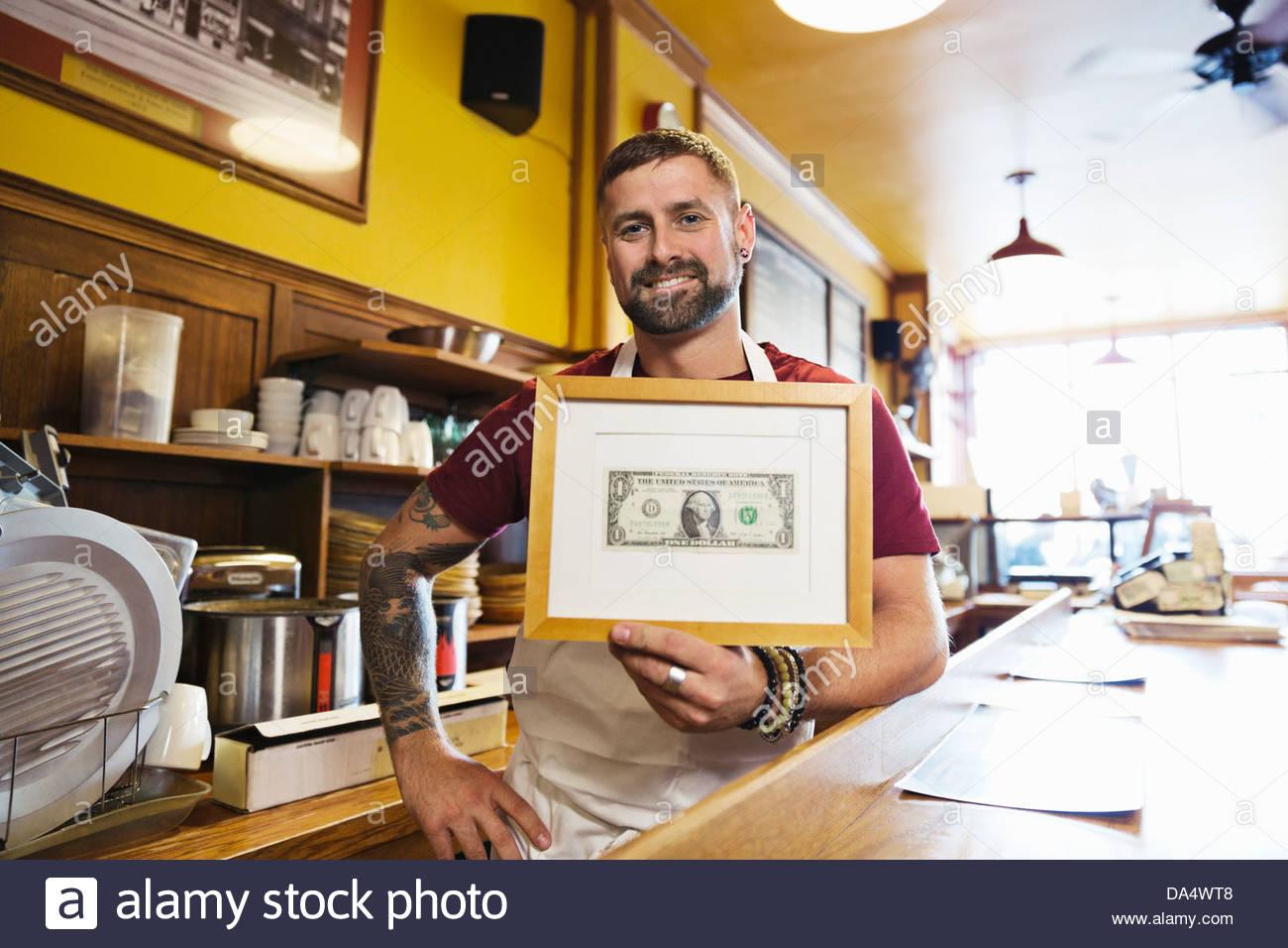 Porträt von männlichen Deli Inhaber halten gerahmt Dollarschein Stockbild