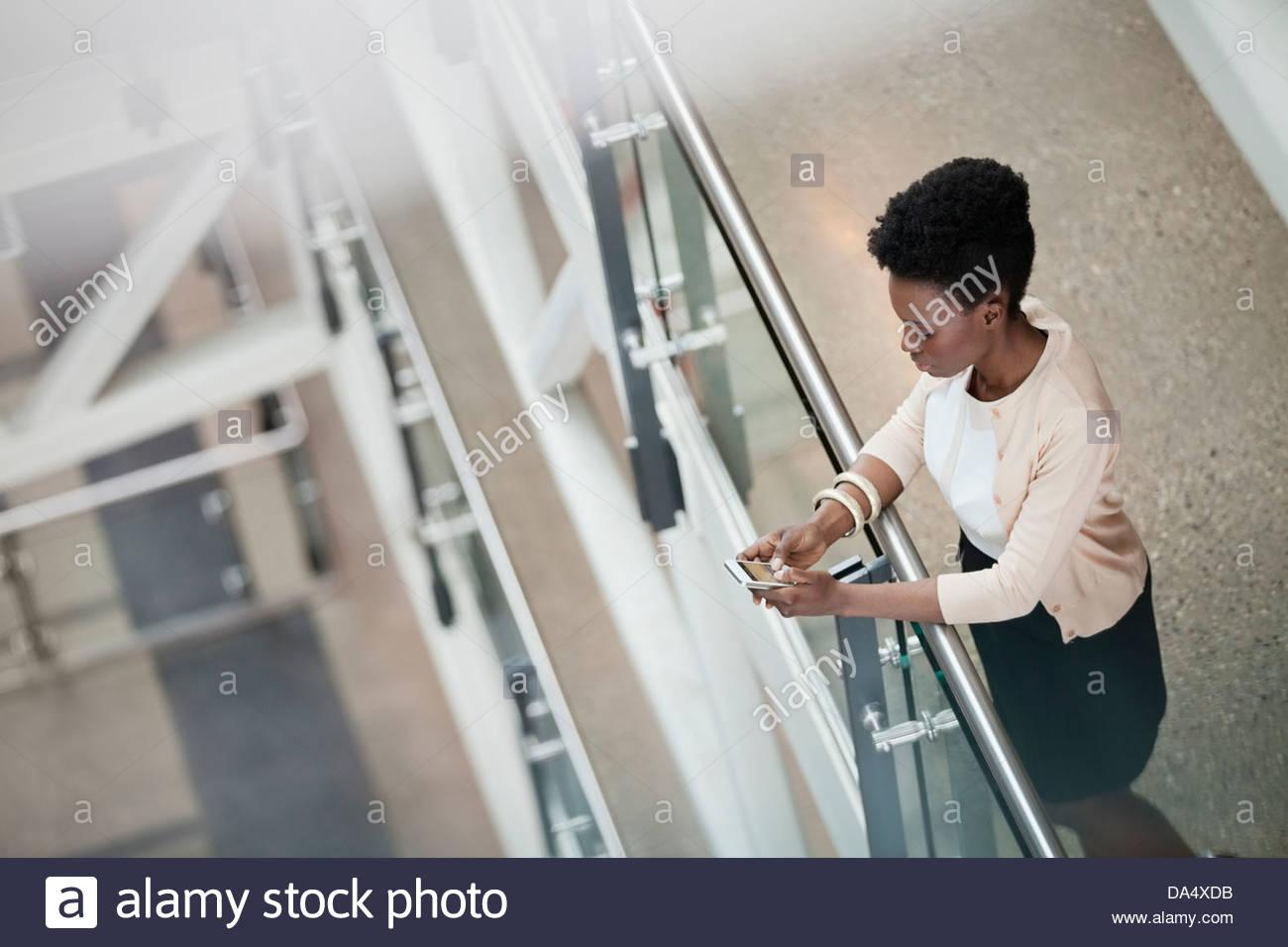 Erhöhte Ansicht von Frau mit Handy im Bürogebäude Stockbild