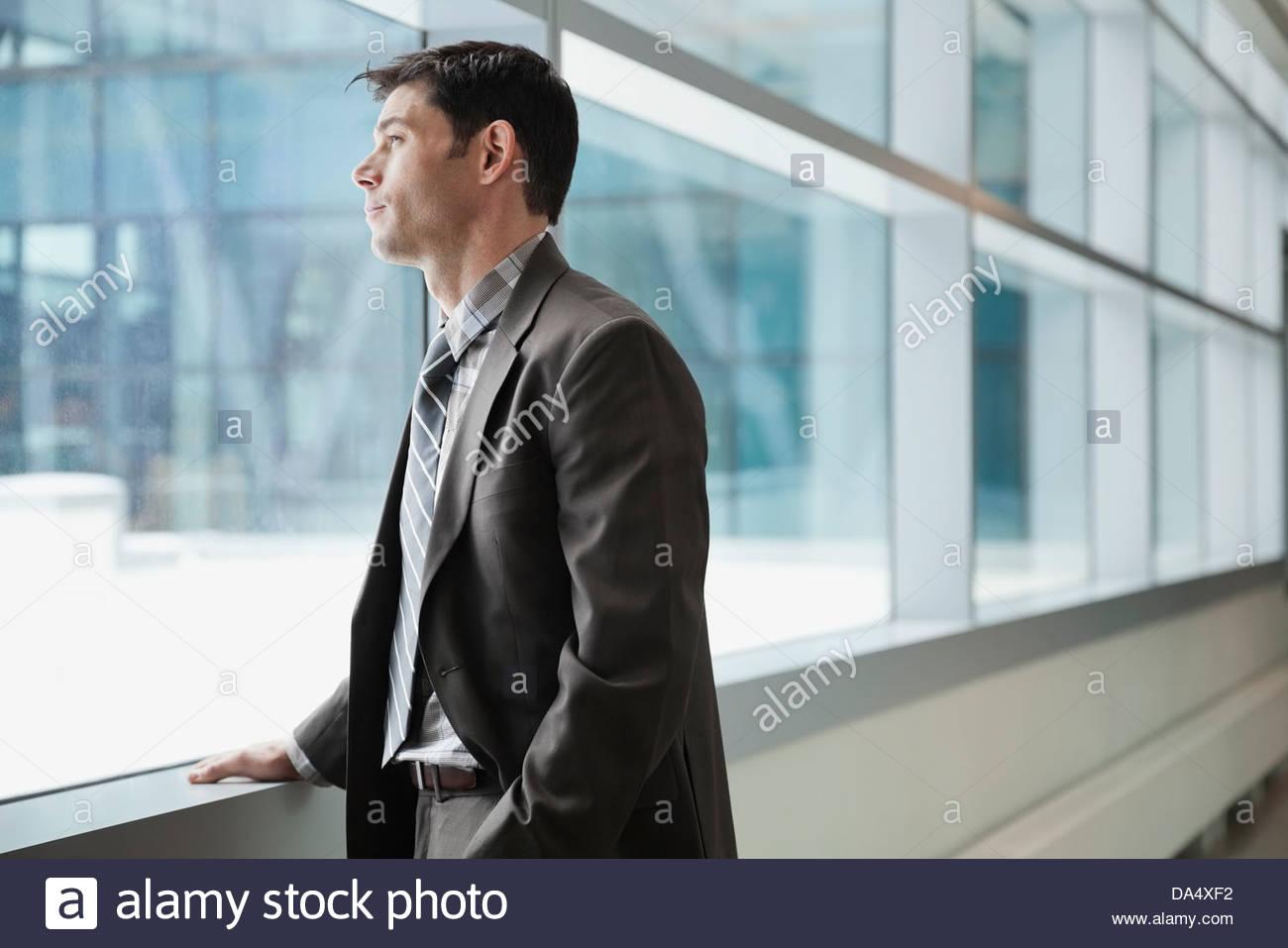 Geschäftsmann aus Fenster im Bürogebäude Stockbild