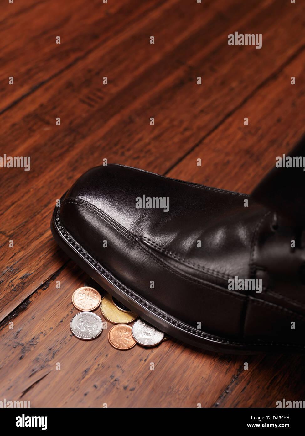 Nahaufnahme von einem Mann Schuh stehen auf Veränderung, Münzen, Geld auf den Boden-Konzept gefunden Stockbild
