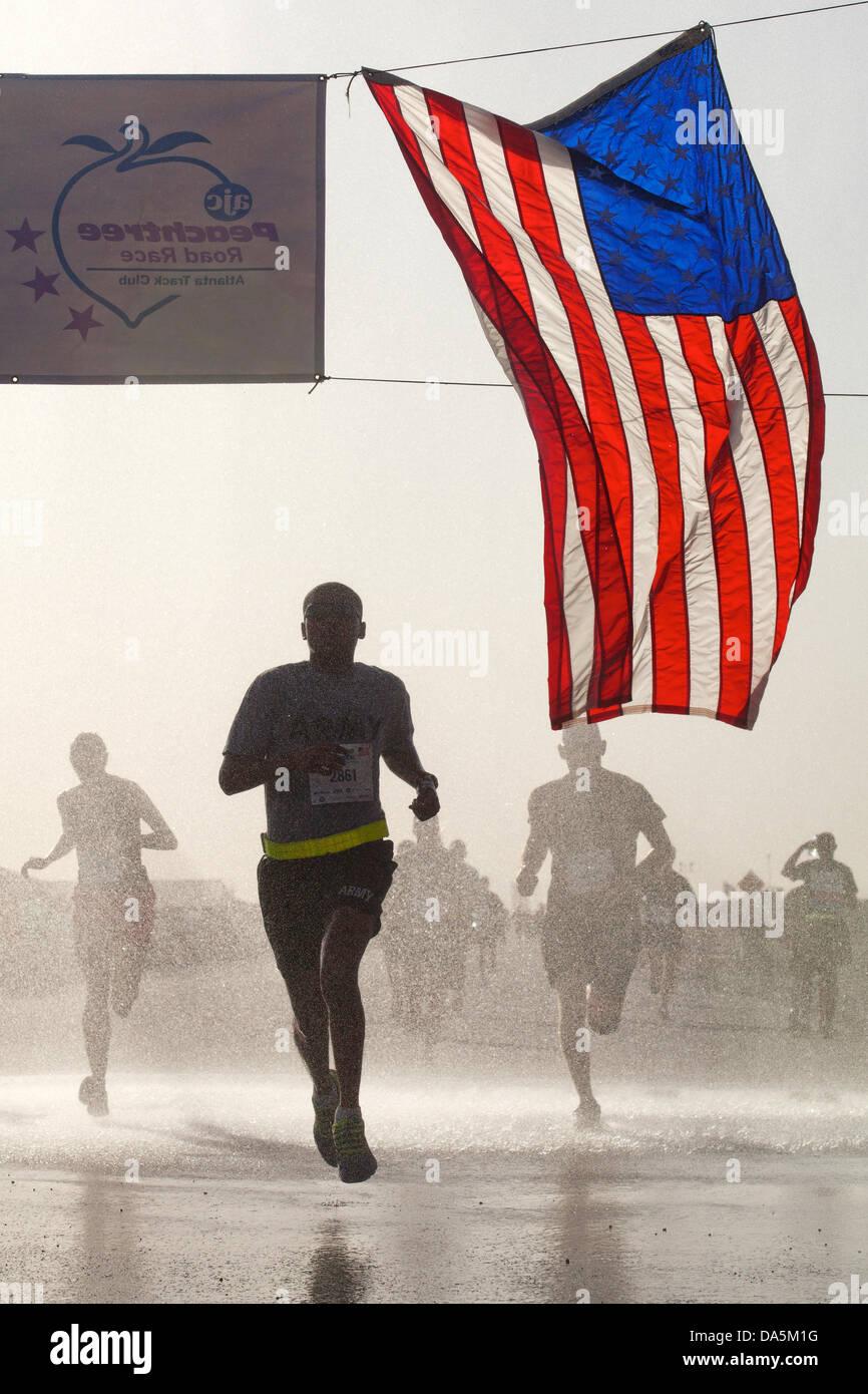Ein Soldat der US-Armee überquert die Ziellinie, während der Teilnahme aus der Ferne in Atlanta Peachtree Stockbild