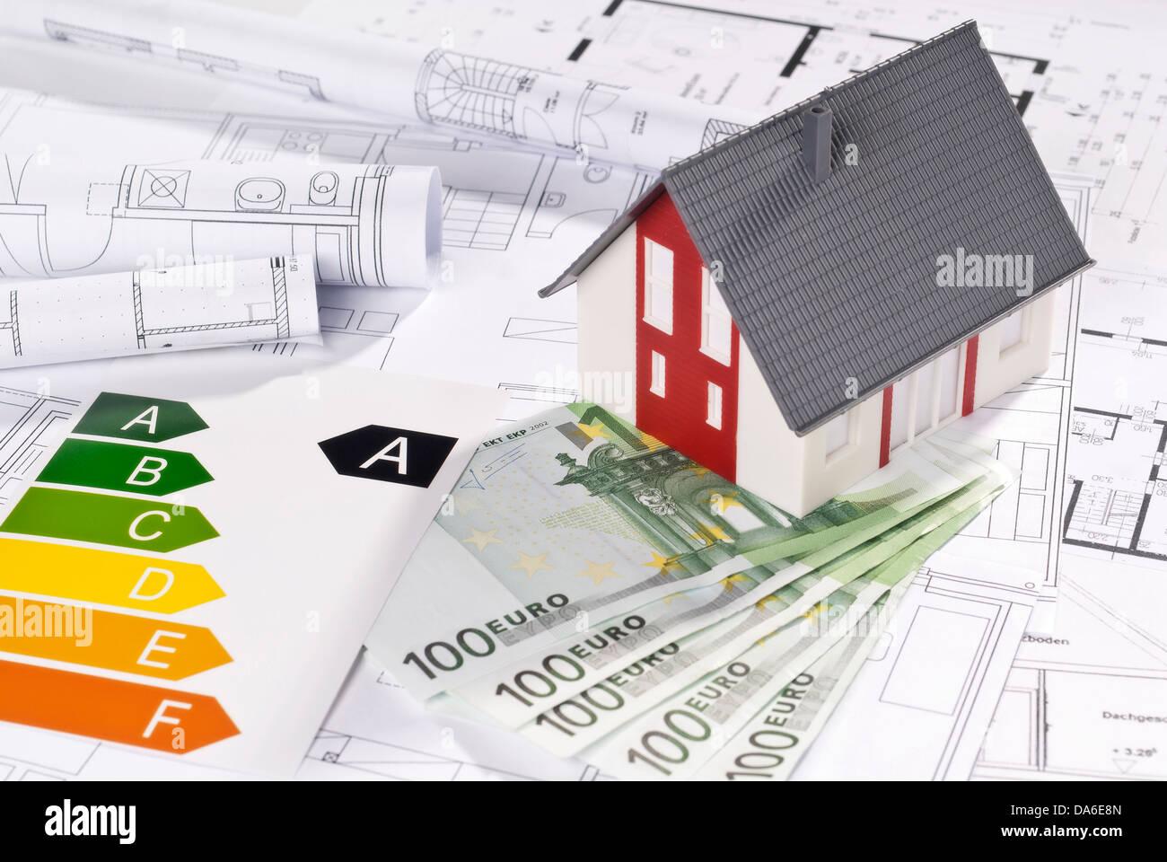 Energieeffizienz-Label mit Architekturmodell, Blaupausen und Rechnungen. Stockbild