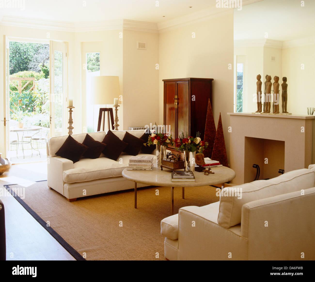 Cremefarbene Sofas einander über Couchtisch Kamin im ...