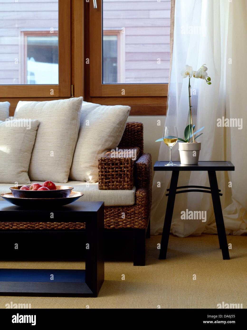 Dunkles Holz Couchtisch Vor Rattan Sofa Mit Weißen Kissen Im Modernen  Wohnzimmer Mit Weißen Voile Vorhänge Am Fenster