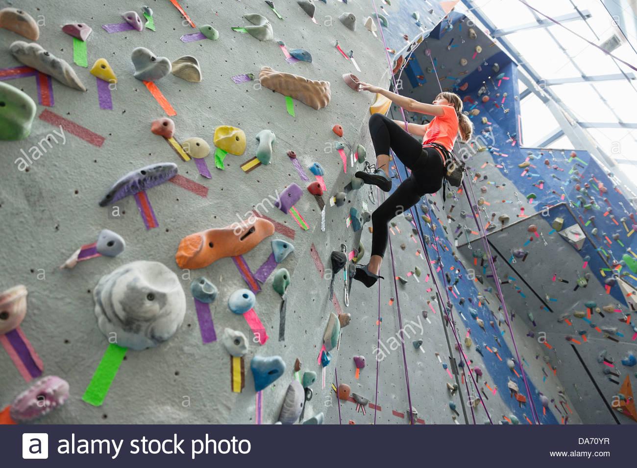 Niedrigen Winkel Ansicht von Frau Klettern an der Kletterwand im Fitnessstudio Stockbild