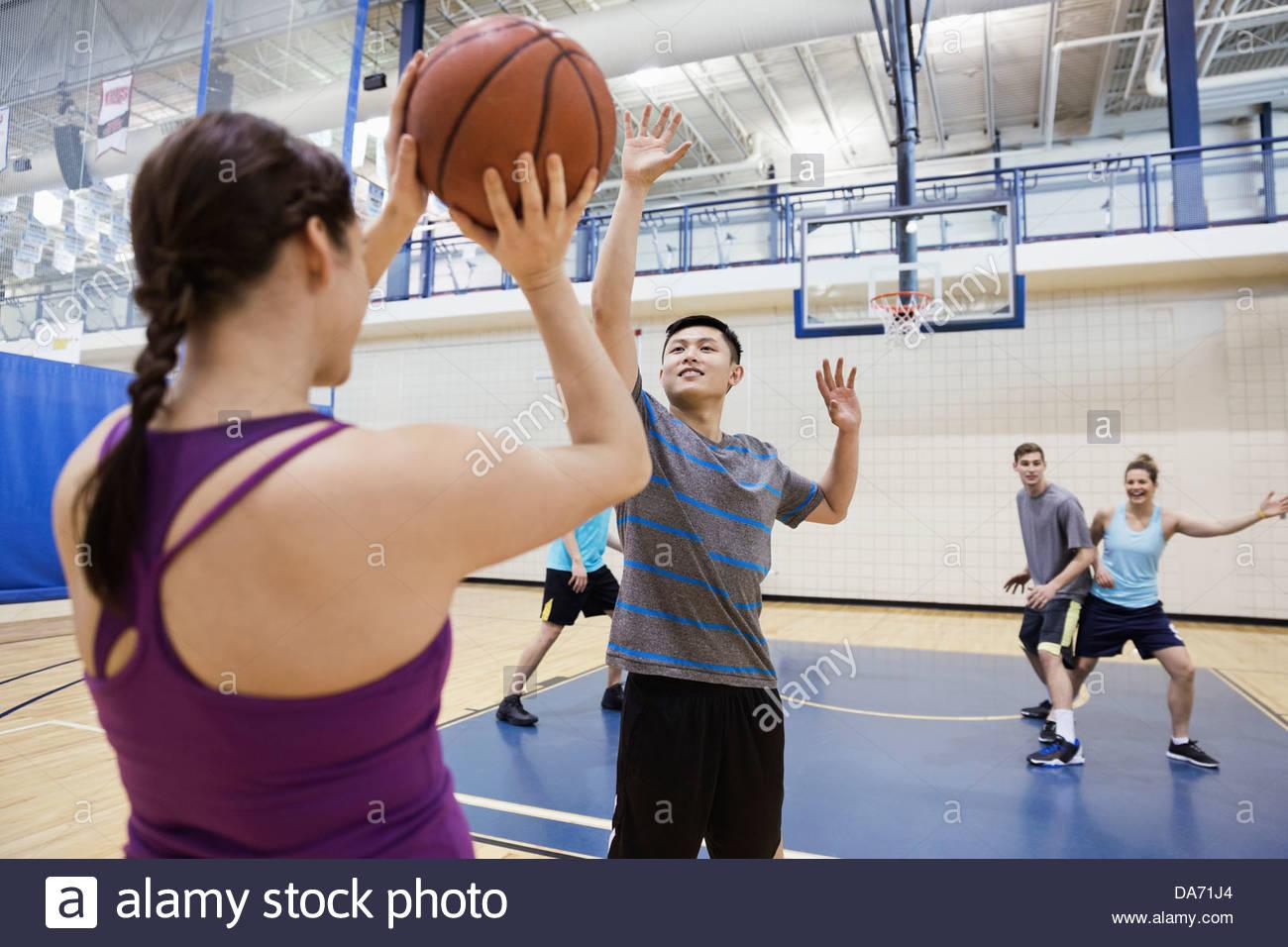 Männer und Frauen spielen Basketball in Turnhalle Stockbild