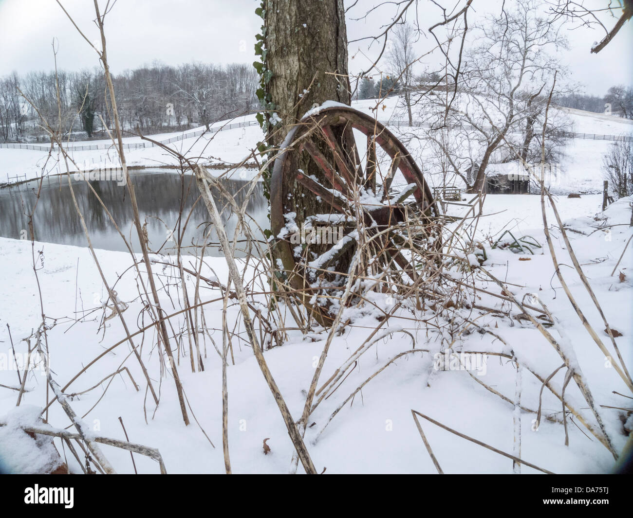 Antikes Wagenrad im Schnee Stockbild