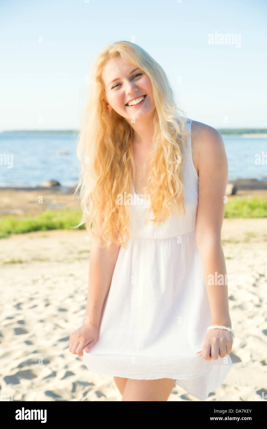 Lächelnde junge Frau im Kleid mit goldenen Haaren Stockbild