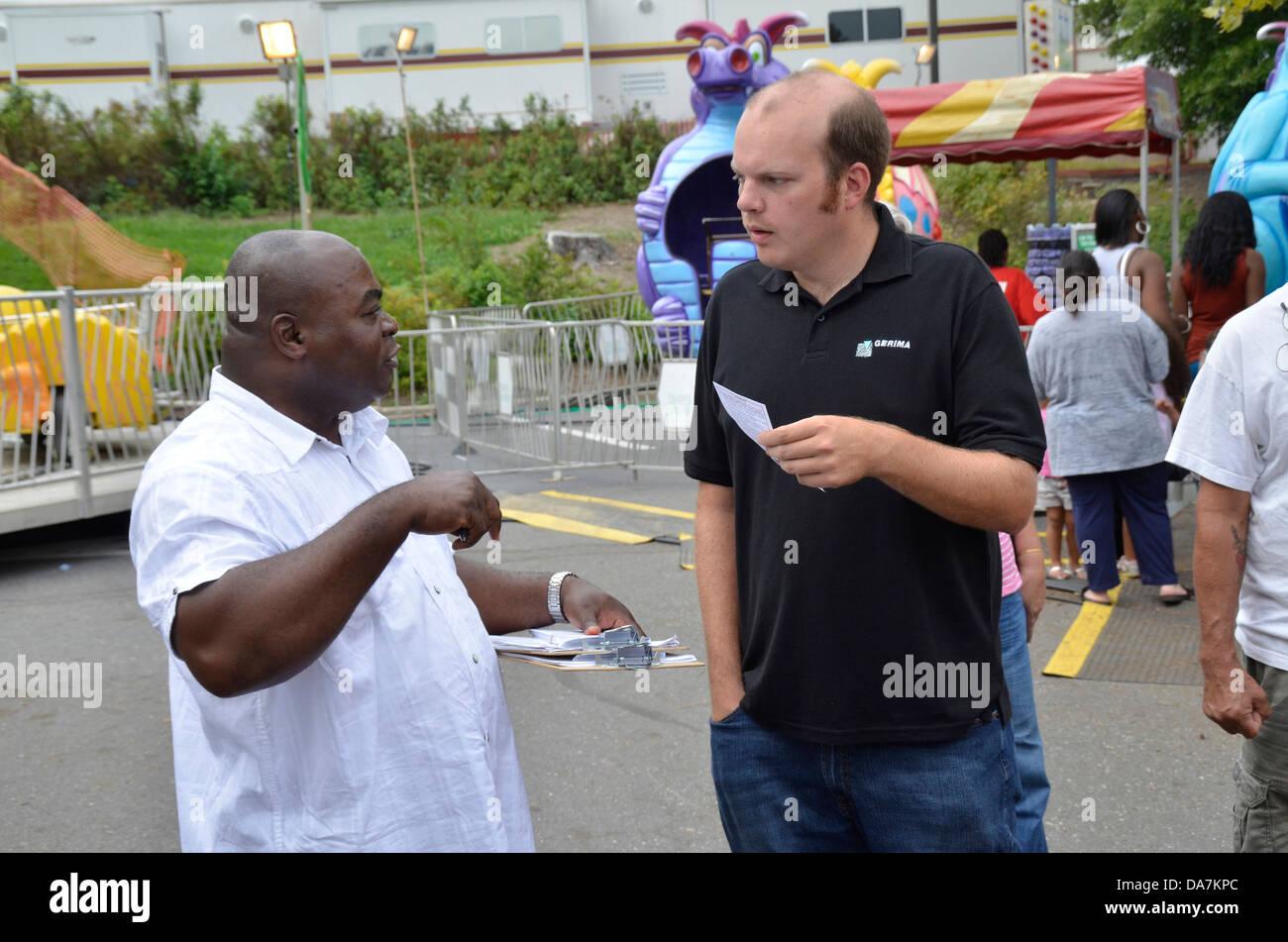 Afrikanischer Mann versuchen, Signatur von einem weißen Mann über Taxi Gesetzgebung auf einem Festival Stockbild