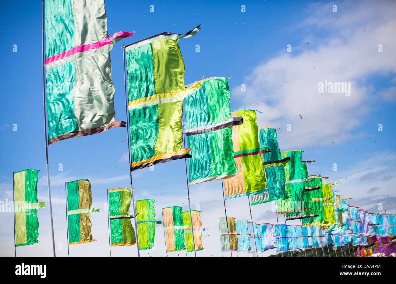 Bunte grüne und blaue Fahnen flattern im Wind am Glastonbury Festival 2013. Stockbild