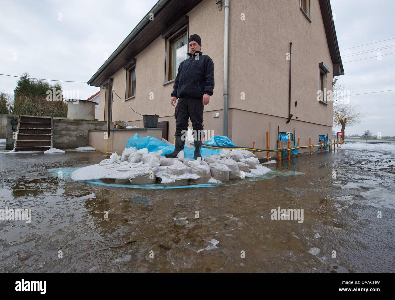 Hauseigentümer Ruediger Ewald steht auf Sandsäcke vor seinem überfluteten Haus während der Flut Stockbild