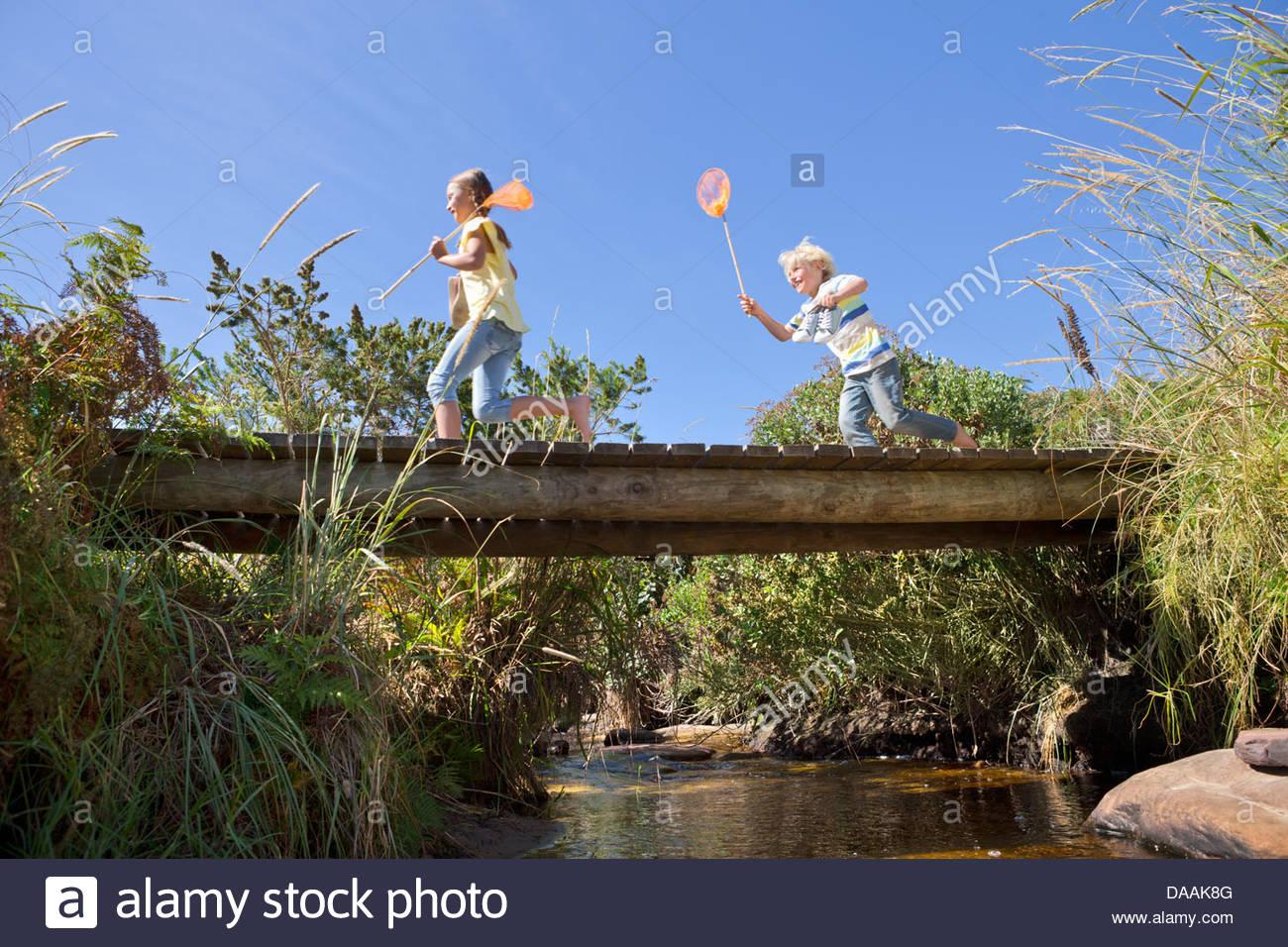 Fröhlicher Junge und Mädchen mit Fischernetzen läuft auf Fußgängerbrücke über Stockbild