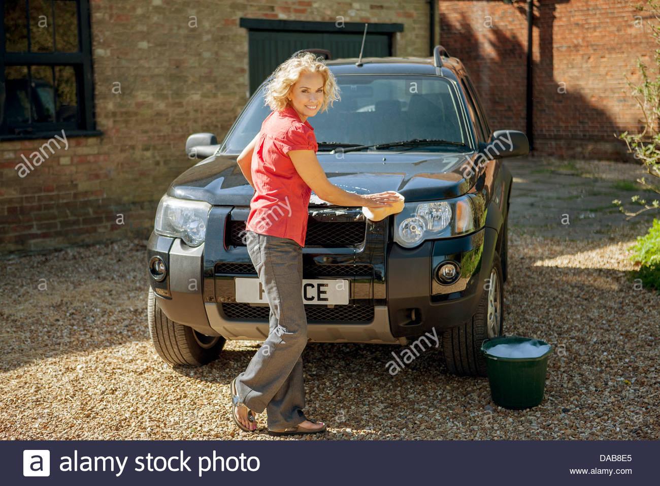 Eine reife Frau, die eine vier-Rad-Antrieb-Auto waschen Stockbild