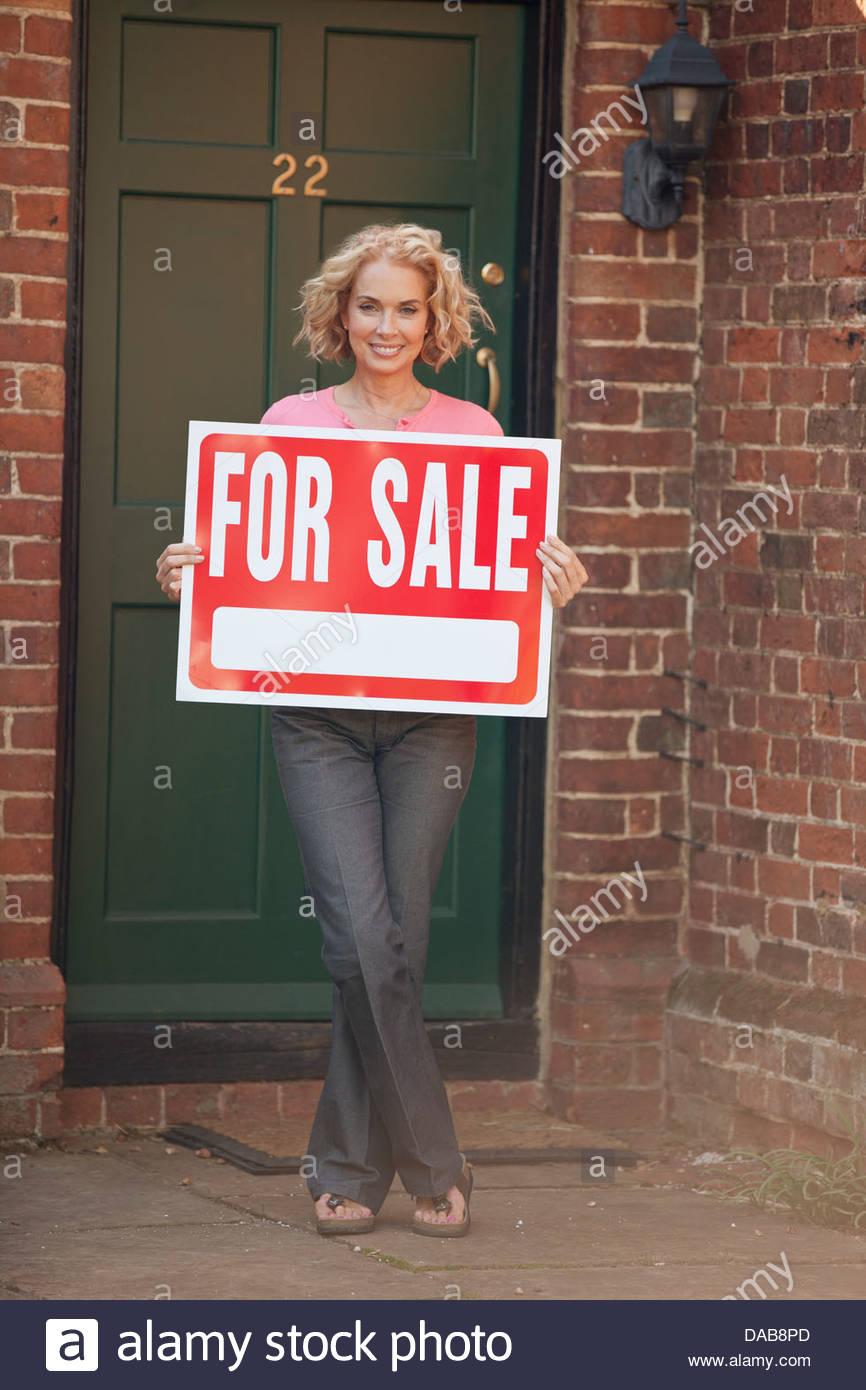 Eine reife Frau hält eine Eigenschaft für Verkauf Zeichen Stockbild