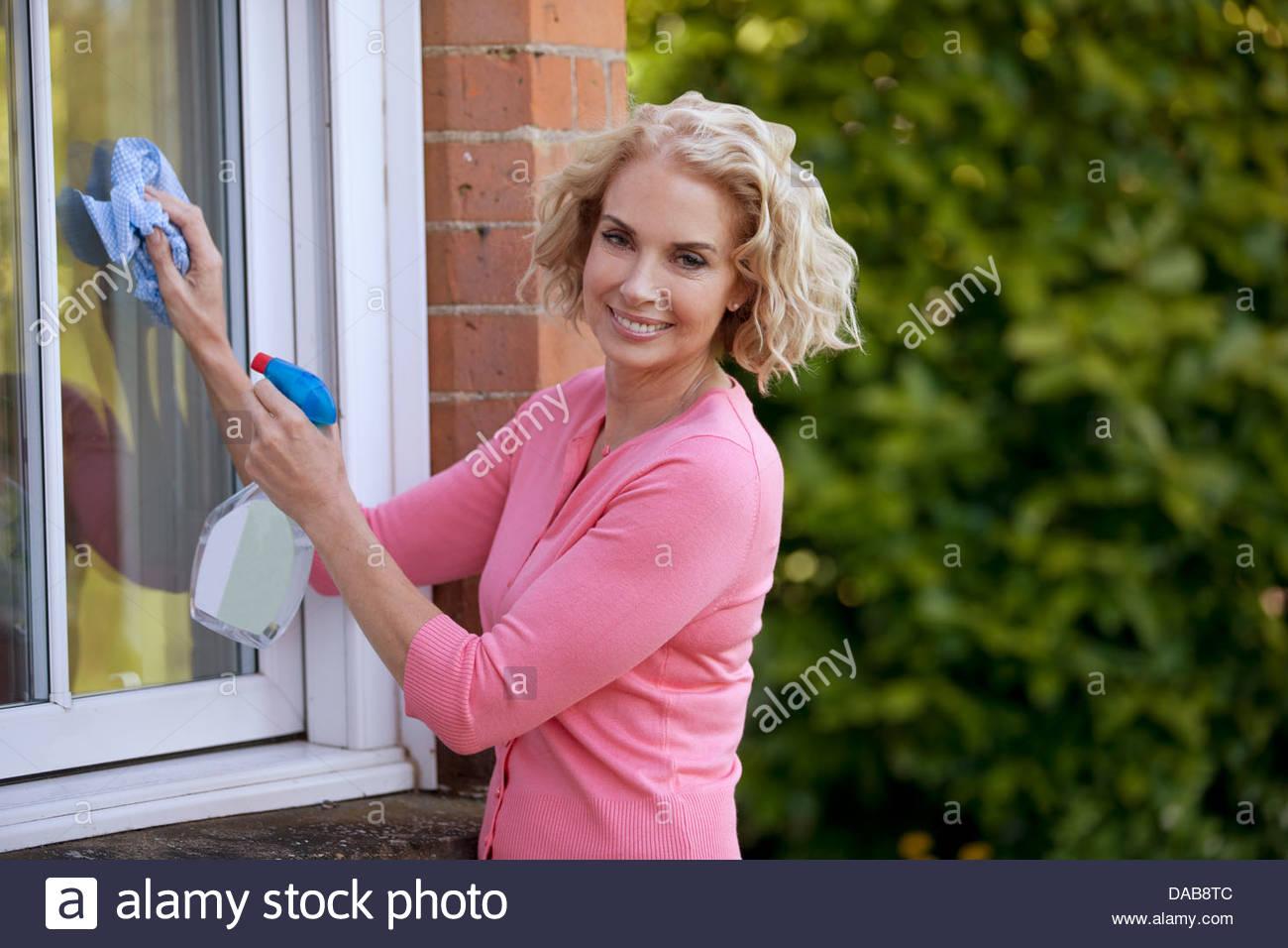 Eine reife Frau, die Reinigung von Fenstern eines Hauses Stockfoto