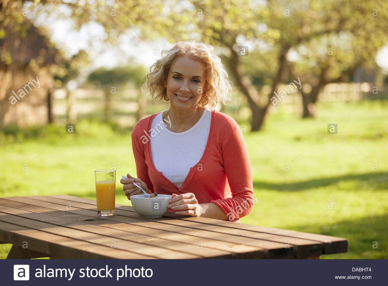 Eine reife Frau sitzen auf einer Gartenbank frühstücken Stockbild