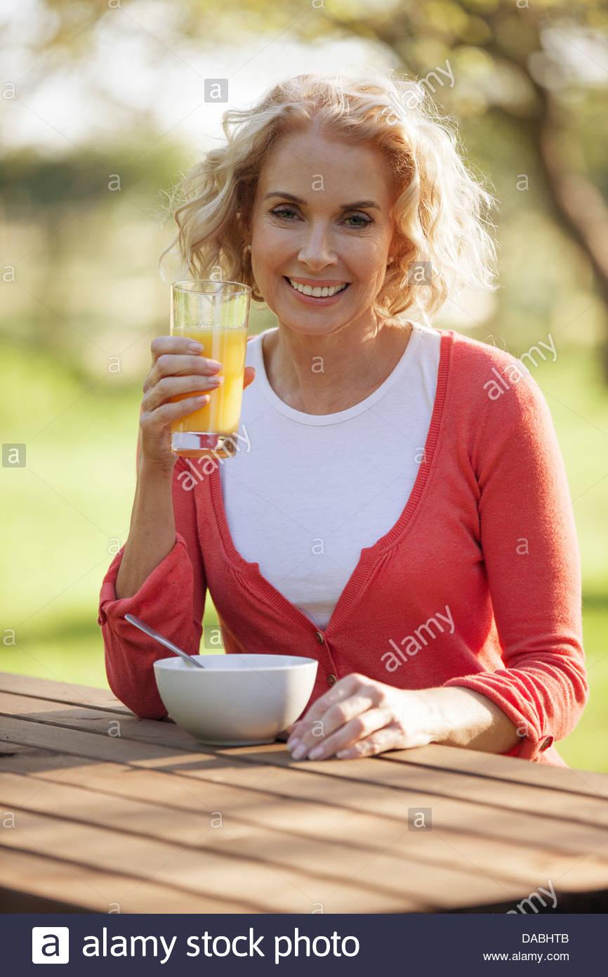 Eine reife Frau sitzen auf einer Gartenbank Orangensaft trinken Stockbild