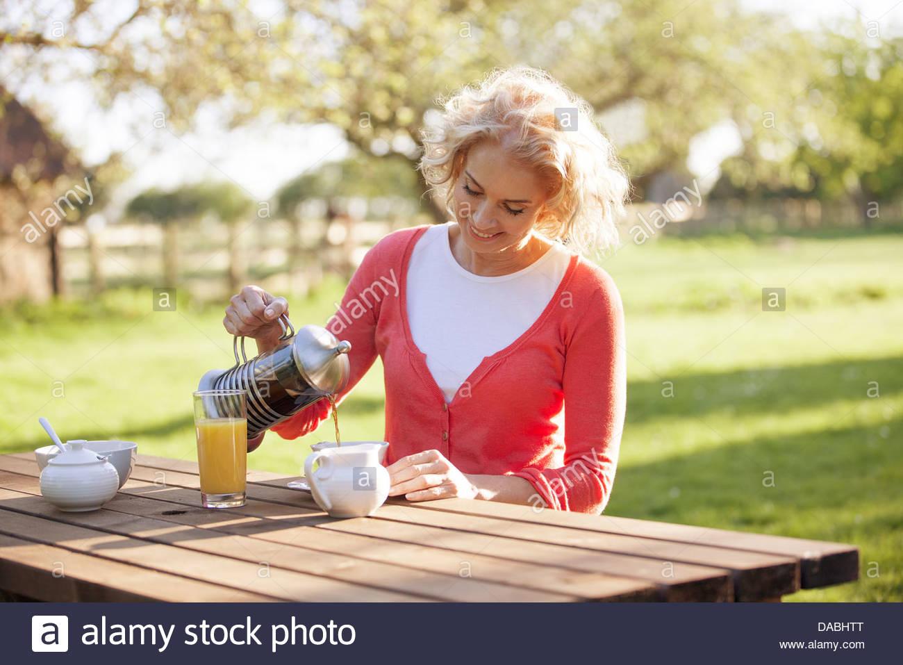 Eine reife Frau sitzen auf einer Gartenbank Kaffee gießen Stockbild