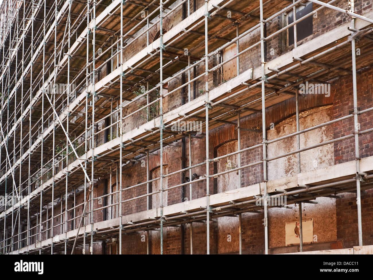 Gerüste, die Unterstützung von eines alten verfallenen Gebäudes Stockbild