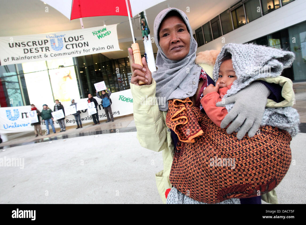 Indonesischer Aktivist Ida und ihr einjähriger Sohn Agung Protest zusammen mit Aktivisten aus der Umweltschutzorganisation Robin Wood vor dem Unilever-Gebäude in der Hafencity in Hamburg, Deutschland, 14. Dezember 2011. Umweltschutz-Aktivisten wollen aufmerksam machen auf die Zerstörung der indonesischen Regenwälder für die Produktion von Palmöl mit dem c Stockfoto