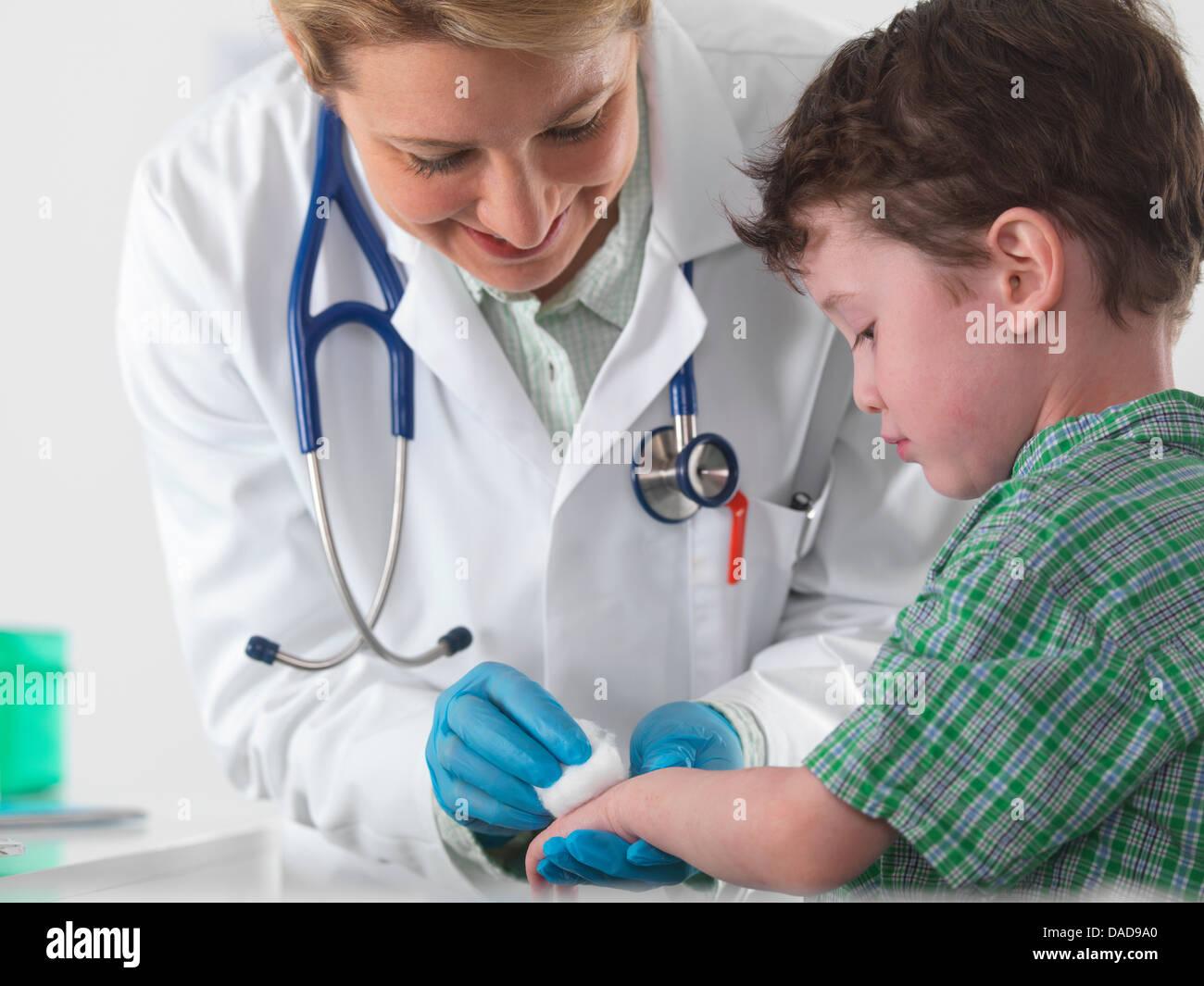 Arzt Pflege für kleine Jungen mit Verletzungen Stockbild