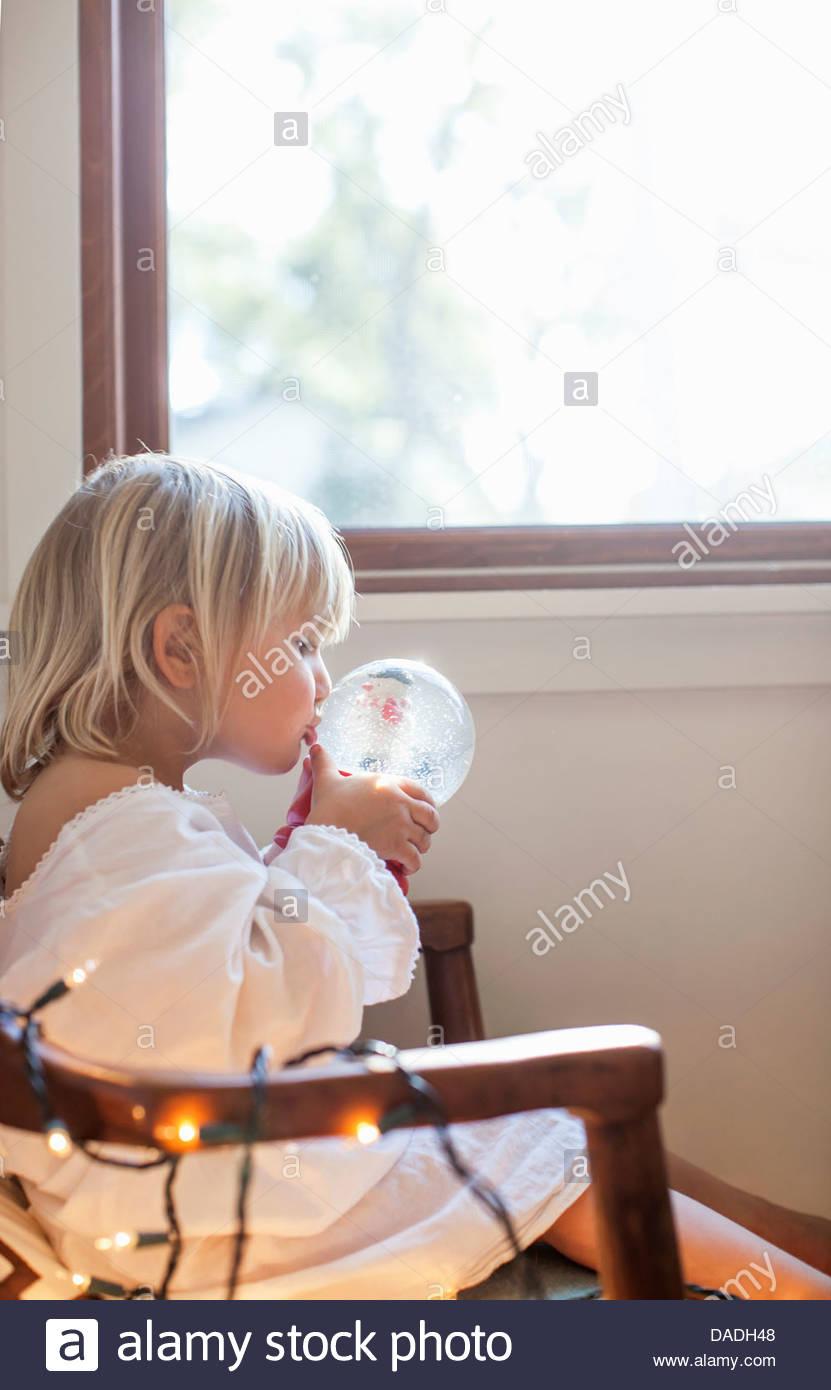 Mädchen küssen Schneekugel Stockbild
