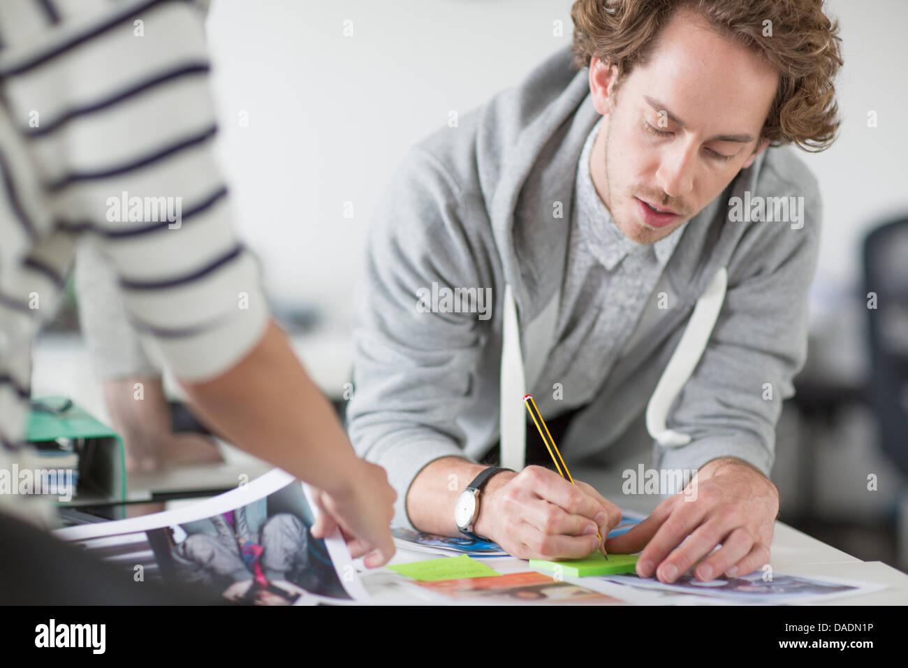 Junger Mann Notizen auf Schreibtisch im Kreativbüro Stockbild