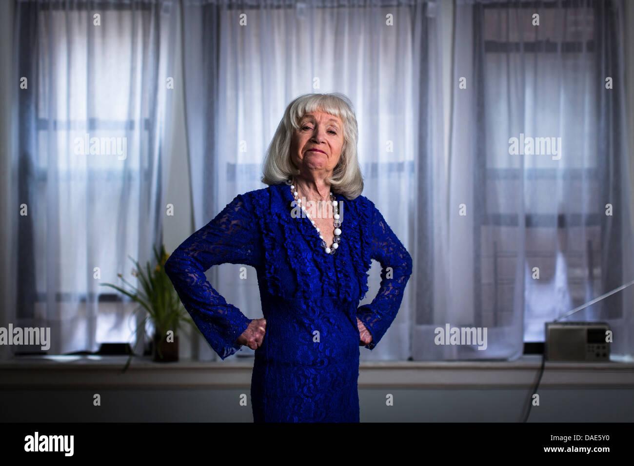 Ältere Frau im blauen Kleid mit Händen auf den Hüften Stockbild