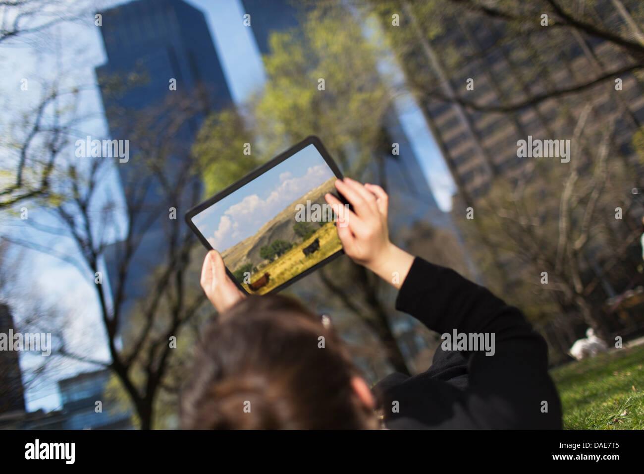 Frau im Stadtpark Blick auf digitale Tablet-Bildschirm Stockbild